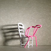 Sad Pink stick figure sitting on a white chair